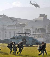 """1月19日,美国海军直升机运载第82空降师士兵在海地总统府前降落。截至18日,美军已向海地派出超过1.1万名军事人员、33架救援专机、""""卡尔·文森""""号航空母舰和多艘军舰。"""