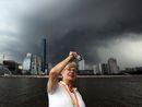 外国记者在广州珠江边拍摄乌云密布的广州市区