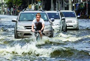 11月6日,在曼谷,一名男子在洪水中骑车前行。新华社/路透