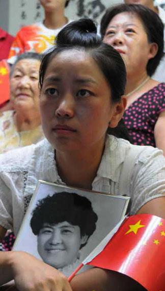 2008年奥运会,曹晶捧着母亲的遗像关注妹妹曹磊争夺金牌