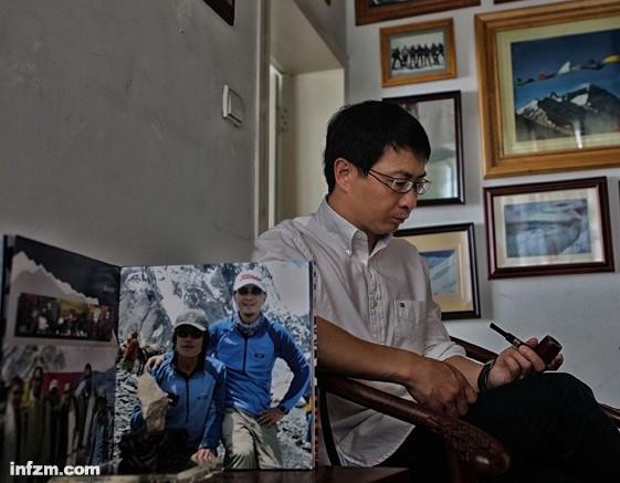 2013年7月2日,张京川低头看着杨春风这次的遗物烟斗,他身边的茶几上放着他和杨春风一起登顶K2时候的照片和带回来的石头。 (南方周末记者 麦圈/图)