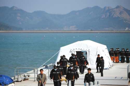 """4月21日,在珍岛的一个港口,救援人员抬着""""岁月""""号沉没客轮遇难者遗体。新华社发"""