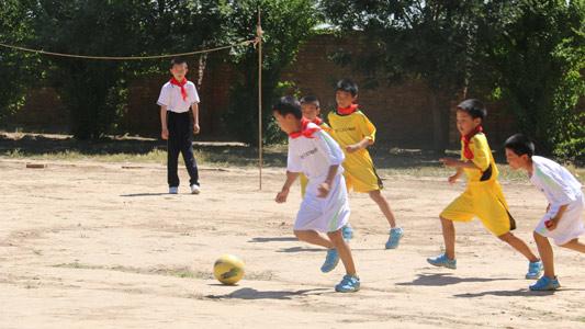 孩子们穿上新的球衣球鞋在自己搭建的简易足球场上踢足球赛