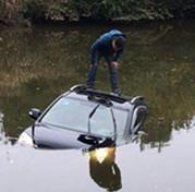 开车玩手机玩进水塘里 民警及时救助死里逃生